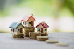 Minihuis op stapel muntstukken, Onroerende goedereninvestering, sparen geld stock afbeelding