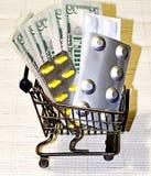 Minikarretje met pillen en dollars Zakgeld op pillen stock afbeeldingen