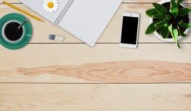 Minimaal werkend huisbureau van creatieve persoon Huismateriaal van lege blocnote, potlood, rubber, mok koffie, smartphone en pot Stock Fotografie