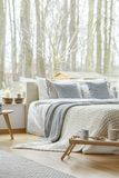 Minimal bedroom interior of house. Blue pillows and blanket on bed in minimal bedroom interior of a house with wooden furniture Royalty Free Stock Photos