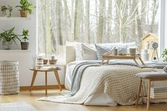 Minimal bedroom interior with plants. Book on wooden table next to bed in minimal bedroom interior with plants and view on forest Royalty Free Stock Photo