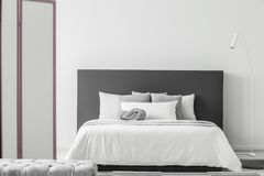 Minimal bedroom interior. White lamp next to a bed with grey bedhead in minimal bedroom interior with pouf and screen Stock Image