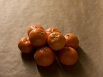 Minimal composition - A pile of clementines on brown paper stock photography