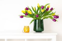 Minimal composition, scandinavian nordic hygge style, home interior, mother day - tulips in green vase, yellow candleholder. White shelf royalty free stock photo