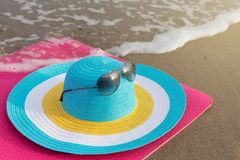 Minimal concept of a beach trip, colorful hat on the beach near the water, on a pink fitness mat royalty free stock photos