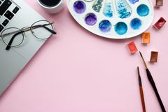 Minimal feminine workspace with laptop, watercolor palette, cuvettes, glasses, mug of coffee, paint brushes on pale pink pastel ba. Ckground Royalty Free Stock Photos