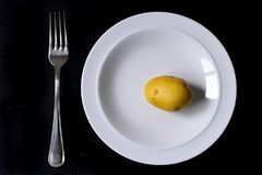 Minimal food in a dish. Minimal food concept in a white dish over a black background Stock Images