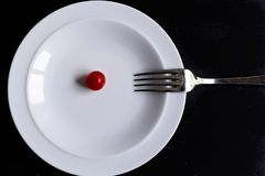 Minimal food in a dish. Minimal food concept in a white dish over a black background Stock Image