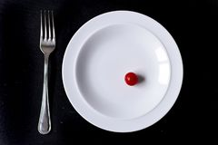 Minimal food in a dish. Minimal food concept in a white dish over a black background Stock Photos