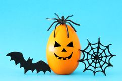 Minimal and funny Halloween holiday concept. Orange egg with scary cute face, spiderweb, bat and spider on top. Minimal and funny Halloween holiday concept royalty free stock photo