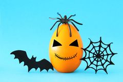 Minimal and funny Halloween holiday concept. Orange egg with scary cute face, spiderweb, bat and spider on top. Minimal and funny Halloween holiday concept royalty free stock image