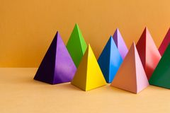 Minimal geometric still life background. Three-dimensional pyramid prism rectangular on orange background. Colorful. Yellow blue pink green violet red colored royalty free stock image