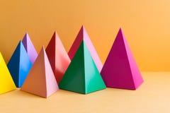 Minimal geometry background. Colorful prism figures on orange backdrop. Simple design concept. Minimal geometry background. Colorful prism figures on orange stock image