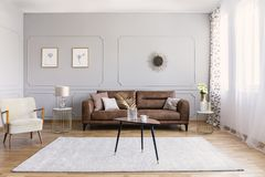 Minimal interior design of living room with brown leather couch, retro armchair coffee table and golden decorations. Real photo stock photography