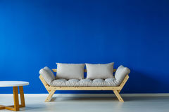 Minimal interior with small table. Minimal interior with a wooden small table, and a cozy looking modern couch Stock Photography