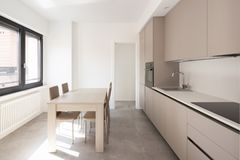 Minimal kitchen in a modern apartment. With chairs and table. Nobody iniside royalty free stock image