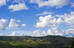 A simple landscape with green rolling hills and white puffy clouds. A minimal landscape with green rolling hills and  white puffy clouds against a clear blue sky Stock Images