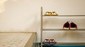 Minimal Metal Shoe Rack with Flip Flops and Red Shoes - Vintage stock photos
