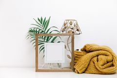 Minimal Mock up wooden frame with green tropical leaves and trendy warm sweater. Nordic decorations, Scandinavian style interior royalty free stock images
