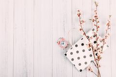 Minimal modern shopping sale background, banner. Blooming cherry branch with flowers, shopping bag and pink alarm clock on light stock image