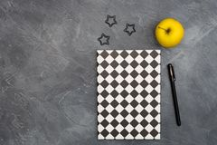 Minimal office concept. Black paper clips, bright yellow apple and pen and closed black-white colored copybook on dark. Black abstract background with copy stock photo