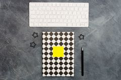 Minimal office concept. Keyboard, lack paper clips, bright yellow sticky note and pen and closed black-white colored. Minimal office concept. Keyboard, Black royalty free stock images