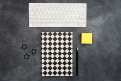 Minimal office concept. Keyboard, lack paper clips, bright yellow sticky note and pen and closed black-white colored. Minimal office concept. Keyboard, Black stock photos