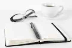 Minimal office still life. Opened notepad with blank linear pages, black pen, glasses and cup of coffee on white background. Soft focus, shallow DOF Royalty Free Stock Photography
