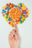 Minimal plat étendu par fond blanc de main de lucette de bonbons au chocolat Photo stock