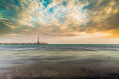 Minimal Sea Scene with Lighthouse and Dramatic Sky Stock Image