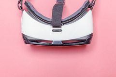 Minimal simple flat lay with virtual reality VR glasses helmet headset on pink pastel trendy modern background. Minimal simple flat lay with virtual reality VR stock image