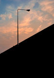 Minimal street light. Bridge and street light surrounded by an intense cloudy sky Royalty Free Stock Image