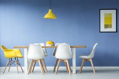 Minimal style dining room. Minimal, modern dining room in interior with a table and contrasting white and yellow chairs around it, against blue wall with a royalty free stock image