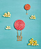 Minimal Travel Fun Concept. Creative Travel Concept - Top View Sweet Red Candy Air Balloons and Popcorn Clouds on Blue Background. Minimal Travel and Food Fun stock photos