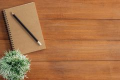 Creative flat lay photo of workspace desk. Office desk wooden table background with mock up notebooks and pencil and plant. Minimal work space - Creative flat royalty free stock image