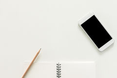 Creative flat lay photo of workspace desk with sketchbook and mobile phone with blank screen on copy space white background. Stock Photos