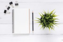 White office desk wooden table background with open mock up notebooks and pens and plant. stock images