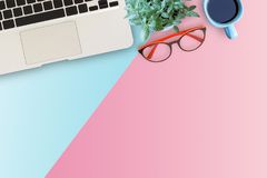 Minimal workspace with Laptop, glasses,flower and smartphone. Copy space on color background. Top view. Flat lay style Stock Photo