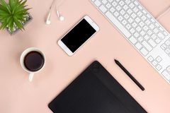 Minimal workspace with technology equipment on pastel pink background royalty free stock image