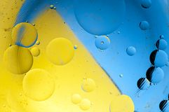 Big oil drops with blue and yellow background stock photo