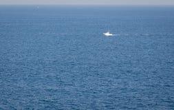 Minimale Ansicht des kantabrischen Meermorgenmeerblicks mit einem einsamen Boot, das mitten in dem Meer schwimmt stockbild