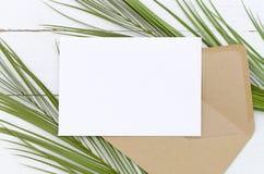 Minimale samenstellings witte lege kaart en envelop op palmbladen op een witte houten achtergrond Model met envelop en royalty-vrije stock afbeeldingen