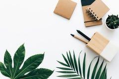 Minimale Schreibtischtabelle mit Briefpapiersatz, -versorgungen und -palmblättern Lizenzfreie Stockfotografie