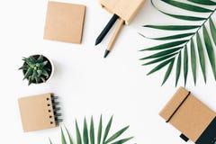 Minimale Schreibtischtabelle mit Briefpapiersatz, -versorgungen und -palmblättern stockfotografie