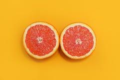 Minimale stijl, creatieve lay-outsinaasappel en grapefruit Vlak leg Het concept van het voedsel De helft van sinaasappel op gele  Stock Foto's