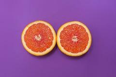Minimale stijl, creatieve lay-outsinaasappel en grapefruit Vlak leg Het concept van het voedsel De helft van sinaasappel op purpe Royalty-vrije Stock Afbeeldingen