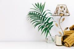 Minimale Zusammensetzung mit grünen tropischen Blättern, Kerze und modischer warmer Strickjacke stockfotos