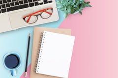 Minimaler Arbeitsplatz mit Laptop, Gläsern, Blume und Smartphone Lizenzfreie Stockfotos