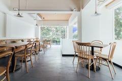 Minimales Brotcafé, das mit weißer Wand und Holzstühlen verziert Warm, gemütlich und bequem stockbilder