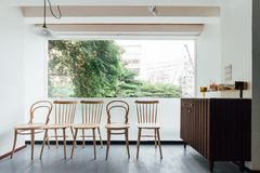 Minimales Brotcafé, das mit weißer Wand und Holzstühlen verziert Warm, gemütlich und bequem lizenzfreie stockbilder